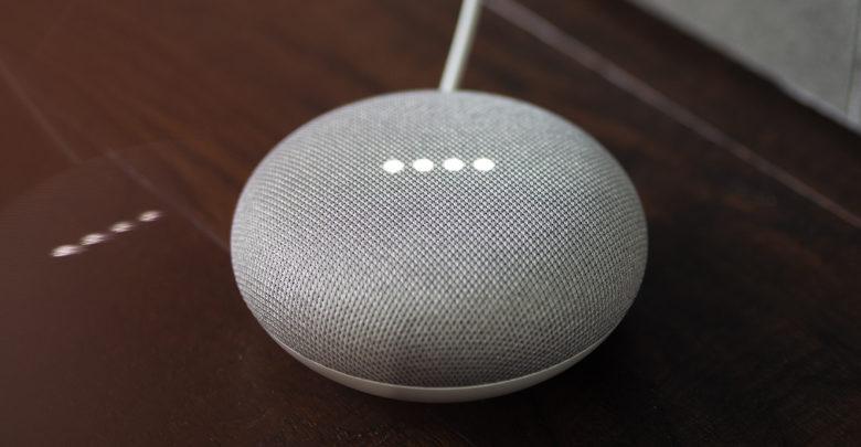 a grey google home mini on wooden floor
