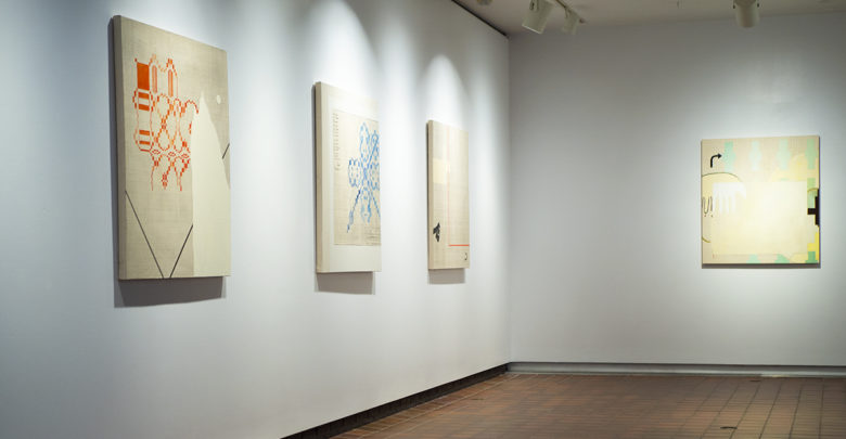 Kim McCollum paintings hanging in a gallery wall